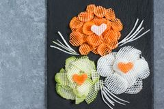 Figured slicing vegetables for vitamin salad to Valentine`s Day. Figured slicing vegetables for vitamin salad. Flowers from carrot, daikon and radishes on slate Stock Photography