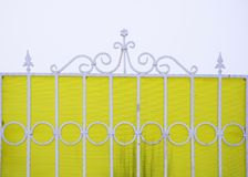 Figured white metal fence on a yellow background. Royalty Free Stock Photo