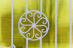 Figured white metal fence on a yellow background. Royalty Free Stock Image