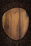 Figured wooden board for the text. On the background of coffee beans, top view Stock Photos