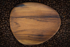 Figured wooden board for the text. On the background of coffee beans, top view, horizontal Royalty Free Stock Photos