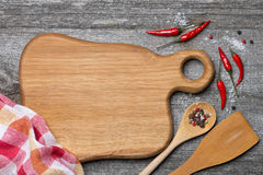 Figured wooden cutting board, spoon, spatula and spices Stock Images