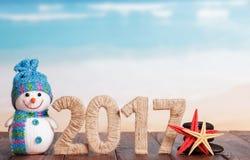 Figuren 2017 sneeuwman en zeester op lijst tegen het overzees Royalty-vrije Stock Afbeeldingen