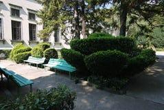 Figurerade blomsterrabatter och bänkar nära enberättelse grånar byggnad Fotografering för Bildbyråer