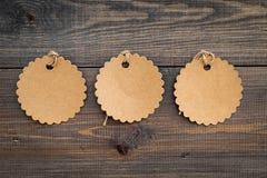 Figurerade tomma etiketter för skriver pris eller avfärdar på mörkt träbakgrundsutrymme för textmodell Royaltyfria Foton
