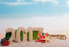 Figures 2017, bottle champagne, stars, gifts in sand against sea. Stock Photo