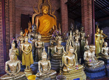 Figures of Buddha covered with gold flakes stock photography