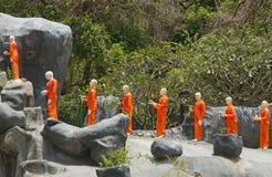 Figures of buddha monkhs in orange dress Stock Image