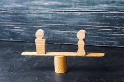 Figures d'un homme et d'une femme sur les échelles concept d'inégalité : l'homme et les femmes sur un pesage équilibrent, espace  Images libres de droits