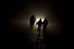 Figures In The Dark. Picture of figures illuminated by vehicle lights Royalty Free Stock Photo