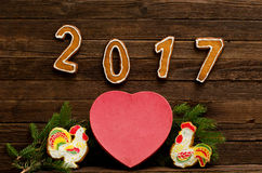 Figures 2017 on a dark wooden background, big heart, two gingerbread rooster and spruce branch. Royalty Free Stock Image