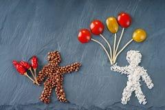 Figures des personnes faites de riz et sarrasin avec les spaghetti, le piment et les tomates Image libre de droits