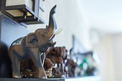 Figures of elephants on shelf. Wooden, stone and ceramic exhibits of collection, happiness and luck at home. Handmade craft. Indoors, copy space royalty free stock image