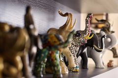 Figures of elephants on shelf. Wooden, stone and ceramic exhibits of collection, happiness and luck at home. Handmade craft. Indoors, copy space royalty free stock photos