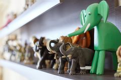 Figures of elephants on shelf. Wooden, stone and ceramic exhibits of collection, happiness and luck at home. Handmade craft. Indoors, copy space stock photography