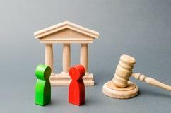 Figures en bois des personnes se tenant près du marteau du juge litige Rivaux d'affaires Conflit d'intérêt la loi et la justice E photographie stock libre de droits