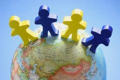 Figures en bois sur le globe Images stock