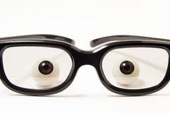 Figures eyes or eyeballs are behind black-rimmed glasses in a slightly darkened glass on a white background. Concept photo for oph. Thalmology, optometry Royalty Free Stock Images