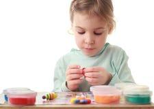 figures försiktigt att flickan little sculpts att sitta Arkivbilder