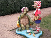 Figures of famous characters of Russian fairy tale, wooden Buratino and old turtle in city park stock image