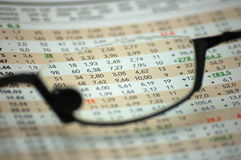 Figures of a financial report through reading glasses. (focus on magazine Royalty Free Stock Photography