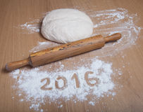 Figures 2016 on a flour on a light wooden table. Selective focus Stock Photos