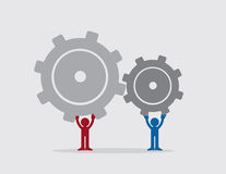 Figures Holding Gears. Two figures putting together large gears Royalty Free Stock Image