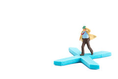 Figures of humans stand on sign x. Miniature businessman toy running on x sign royalty free stock photography
