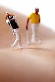 Figures miniatures jouant au golf Images stock