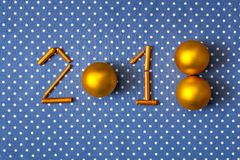 Figures New Year 2018 golden christmas balls and gilt sticks on a cloth background in polka dots Royalty Free Stock Photos