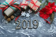 Figures 2019. New year of the pig. Festive Christmas composition with gifts, boxes, cones, walnuts, red flowers poinsettia on a wo royalty free stock image