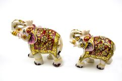 Figures of a pair of white elephants in marble with red and gold painting isolated on white background stock images