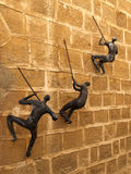 Figures of the people clambering on a wall. Yaffo, Israel Royalty Free Stock Photos