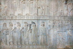Figures of people on the destroyed stone bas-relief in Persepolis Stock Photos