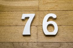 Seventy-six figures on a wooden parquet floor. Figures seventy-six on a wooden, parquet floor as a background Royalty Free Stock Photo