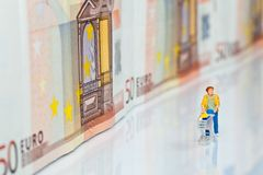 Figures with Shopping Cart and bank notes Stock Photos