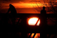 Figures silhouettées contre un coucher du soleil de flambage au parc de crique d'Euclid image stock