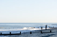 Figures silhouetted on an evening beach in England. Royalty Free Stock Photography