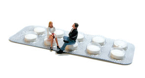 Figures sitting  on pills Stock Photo
