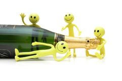 Figures of Smiley around bottle of champagne. Figures of Smiley around a bottle of champagne Royalty Free Stock Photography