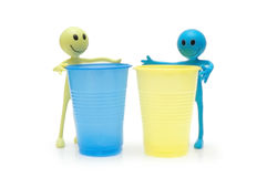 Figures of Smileys and two plastic cups royalty free stock photos