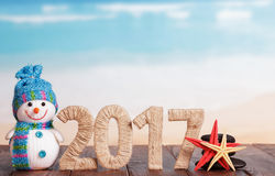 Figures 2017 snowman and starfish on table against the sea. Royalty Free Stock Images