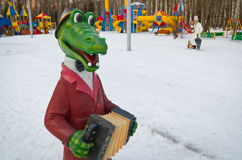 Figures from Soviet cartoons. Crocodile Gena plays the harmonica in the Central Park named after Belousov. Winter evening Stock Image