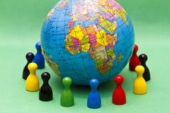 Figures surrounding globe Royalty Free Stock Image