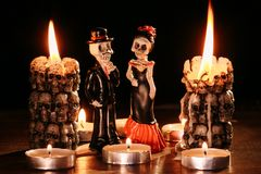 Halloween: figures of two skeletons of the man and the woman against the background of the burning candles in the form Royalty Free Stock Images