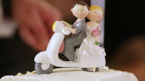 Figures on wedding cake. Wedding figurines in form of motorcyclists on background cutting wedding cake stock video footage