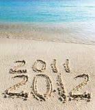 Figures written on beach sand. On sand at ocean edge it is written 2011-2012 Royalty Free Stock Photo
