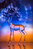 Figurilla cristalina del reno delante de la aurora colorida fotografía de archivo