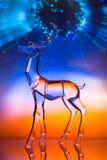 Figurilla cristalina del reno delante de la aurora colorida imagen de archivo