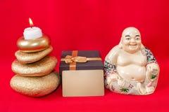 Figurilla de un Buda de risa con piedras y una vela, y una caja de regalo y una tarjeta de visita con el texto libre, en un fondo fotografía de archivo